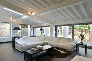 Modernes Wohnzimmer in Schwarz-Weiß mit großer Fensterfront unter Dachschräge
