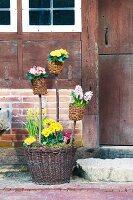 Rustic arrangement of spring flowers and wicker baskets next to front door