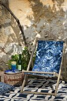 Deckchair and blue textiles in summery seating area