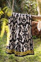 Ornately patterned towel hanging in garden