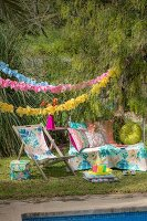 Deckchair and cushions below garlands in colourful seating area in garden