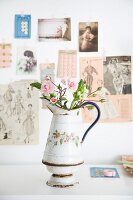 Roses in old enamel jug in front of vintage-style pictures on wall