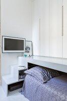 Pull-out bed under wardrobes on platform accessed via steps
