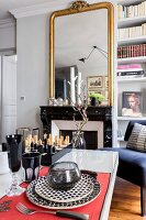 View across set table to gilt-framed mirror above open fireplace