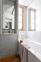 Marble bathtub and narrow sink in small bathroom