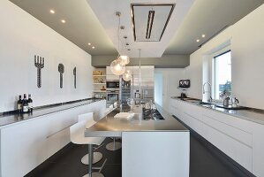 Island counter and long, minimalist base units in modern kitchen