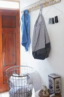 Bag made from striped fabric and old denim hung from coat rack