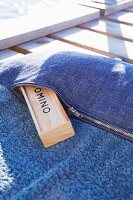 Beach towel with sewn-on denim pocket