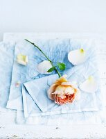 Rose and rose petals lying on blue linen napkin