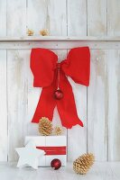 Wrapped gift and golden pine cones below large red bow on white board wall