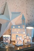Village of illuminated, ceramic, house-shaped tealight holders in front of large white star