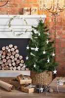 Small Christmas tree decorated with paper stars and wrapped gifts in front of fireplace with mantelpiece
