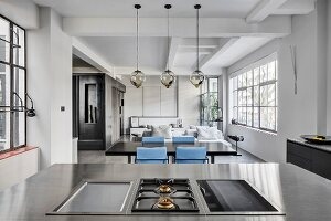 View across hob into living-dining area of industrial loft apartment in shades of grey