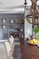 Solid wooden table, cane-backed chairs and open-fronted shelves in dining room