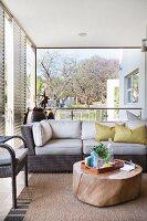 Sofa and slice of tree trunk used as coffee table on veranda