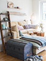 Rustic trunk and ladder-style shelves next to pale yellow corner sofa in living room