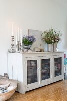 Lit candles in candlesticks and vases of flowers on white sideboard