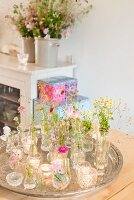 Small glass vases of flowers and tealights on silver tray in front of flowers on sideboard