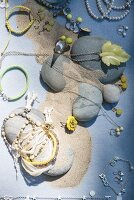 Jewellery amongst pebbles and sand on pale blue surface