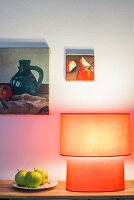 Red lamp, three apples and two paintings