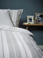 Detail of striped bed linen and bedside table in background