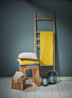 Yellow cloth draped over wooden ladder used as rack and stack of cushions on wooden stool