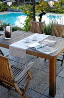 Wooden table and chairs on terrace next to pool