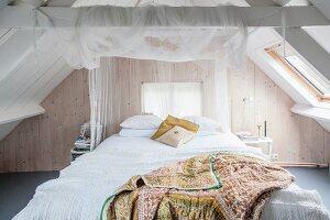Romantic attic bedroom with board walls