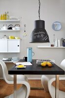 Black and white furniture and writing on chalkboard lamp in dining room