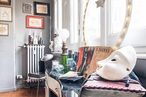 White mask in foreground and flea-market finds on table in front of window