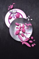 Arrangement of pink nuts and leaves on plates