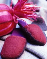 Decorative arrangement of deep pink felt slippers and felt hot-water bottle