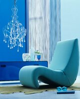 Organic easy chair in blue interior with modern chandelier