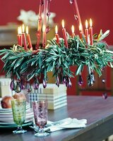 Festive wreath of olive branches, lit red candles and purple crystal pendants hung from ribbons