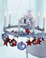 Lit white candles in modern, metal candle wreath decorated with Christmas baubles