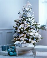 Christmas tree romantically decorated with wing-shaped ornaments and pastel blue baubles in elegant, vintage-style interior