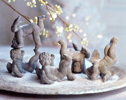 Various terracotta cherubs amongst artificial snow on plate