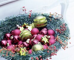 Various shiny and matt Christmas baubles in festive bowl