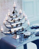Lit white pillar candles on elegant candle holder shaped like a tree
