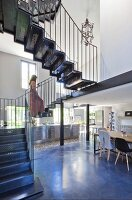 Woman walking up delicate metal staircase in loft apartment in shades of grey