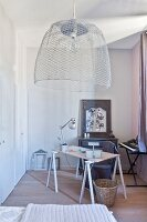 Lampshade hand-crafted from chicken wire above desk on trestles