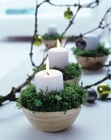 Arrangement of candles, moss and branch