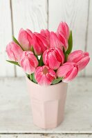 Pink tulips in pale pink vase