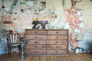 Vintage chest of drawers against rustic stone wall