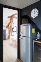Kühlschrank unter der Schräge mit Uhr, Blick ins Wohnzimmer