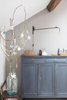 Paper decorations hanging from branch in front of grey cabinet