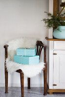 Two gifts on sheepskin on corner chair