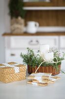 Painted seagrass coasters in front of Christmas arrangement in copper cake tin