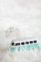 Miniature VW bus amongst pile of white fluffy rug