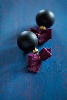 Black Christmas-tree baubles with felt ribbons